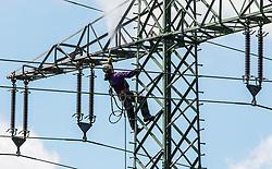 July 13, 2017 - Munich, Bavaria, Germany - Photographer: Sachelle Babbar Two linesman (powerline workers or Netzelektriker) maintain high-voltage power lines on a tower in Munich, Germany. (Credit Image: © Sachelle Babbar via ZUMA Wire)