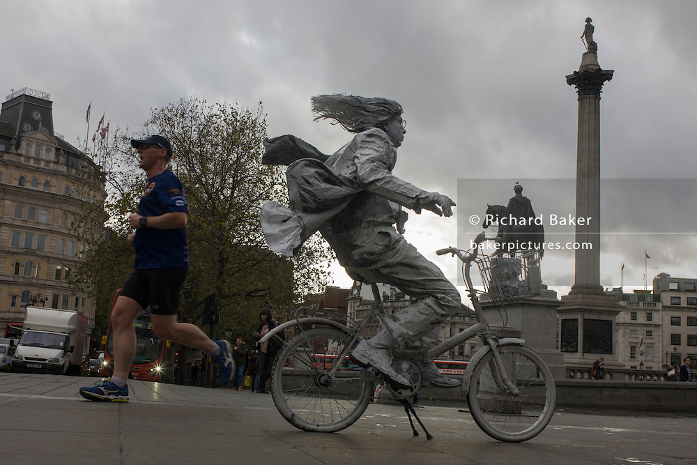 A jogger runs through Trafalgar Square, passing a street artist busker on a painted bike.