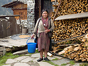 Portrait of a Brokpa woman wearing her traditional clothing outside her home in the remote village of Merak in Eastern Bhutan. The Brokpa, the semi-nomads of the villages of Merak and Sakteng are said to have migrated to Bhutan a few centuries ago from the Tshona region of Southern Tibet. Thriving on rearing yaks and sheep, the Brokpas have maintained many of their unique traditions and customs.