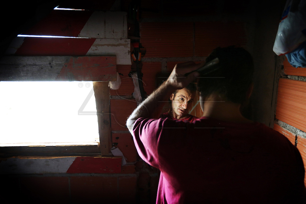 João combs his hair in front of a mirror before leaving the condo to try to obtain the social subvention from the state.