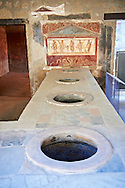 The Thermopolium of Lucius Vetutius Placidus on the Via del Abbondante, with the serving counter with holes that contained amphora of food for sale. The Thermopolium was an eating & drinking house. The painting depicts at the centre the God of the patron and on either side are the lars or protectors of the house, Mercury , God of Commerce & Dionysus, God of wine. .<br /> <br /> If you prefer to buy from our ALAMY PHOTO LIBRARY  Collection visit : https://www.alamy.com/portfolio/paul-williams-funkystock/pompeii.html<br /> Visit our CLASSICAL WORLD HISTORIC SITES PHOTO COLLECTIONS for more photos to buy as buy as wall art prints https://funkystock.photoshelter.com/gallery-collection/Classical-Era-Historic-Sites-Archaeological-Sites-Pictures-Images/C0000g4bSGiDL9rw