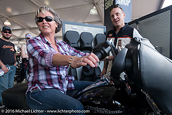 """Sara Beck of Jacksonville, FL checks out handlebar fitting in the """"Fit Shop"""" area of the Harley-Davidson area in Daytona International Speedway during the Daytona Bike Week 75th Anniversary event. FL, USA. Saturday March 5, 2016.  Photography ©2016 Michael Lichter."""