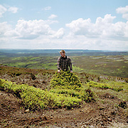 A gamekeeper dragging a turf removed from the moor to make a new grouse shooting butt, Bransdale, North York Moors, North Yorkshire, UK