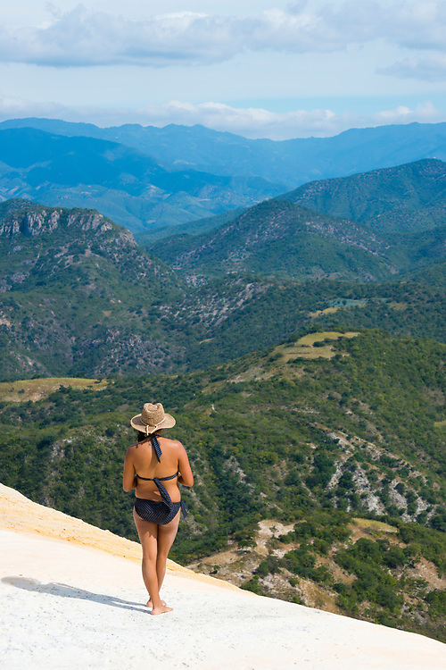 A woman enjoys the scenic view at Hierve el Agua in Oaxaca State, Mexico. The rock formation on which she stands is created by fresh water springs, whose water is over-saturated with calcium carbonate and other minerals.