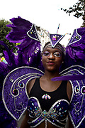 Notting Hill Carnival 2016 Childrens Day. A young girl wearing a purple costume decorated with feathers and jewels takes part in the parade.