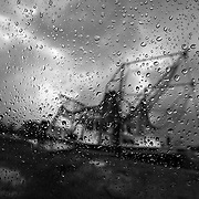 """Louisiana fisherman are suffering as large areas have been closed to commercial fishing because of the the growing oil spill in the Gulf of Mexico. This depression in economic livelihood is illustrated here by a shrimping boat, seen through raindrops on a window and under stormy skies in Galliano, Louisiana. The U.S. Gulf coast accounts for about 20 percent of the nation's total commercial seafood production. The shrimp and oyster supply, in particular, is very concentrated in the Gulf. ltqmb """"Stormy Horizons"""""""