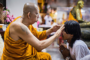 """15 MARCH 2014 - NAKHON CHAI SI, NAKHON PATHOM, THAILAND: A senior monk at Wat Bang Phra blesses a man at the beginning of the tattooo festival. Wat Bang Phra is the best known """"Sak Yant"""" tattoo temple in Thailand. It's located in Nakhon Pathom province, about 40 miles from Bangkok. The tattoos are given with hollow stainless steel needles and are thought to possess magical powers of protection. The tattoos, which are given by Buddhist monks, are popular with soldiers, policeman and gangsters, people who generally live in harm's way. The tattoo must be activated to remain powerful and the annual Wai Khru Ceremony (tattoo festival) at the temple draws thousands of devotees who come to the temple to activate or renew the tattoos. People go into trance like states and then assume the personality of their tattoo, so people with tiger tattoos assume the personality of a tiger, people with monkey tattoos take on the personality of a monkey and so on. In recent years the tattoo festival has become popular with tourists who make the trip to Nakorn Pathom province to see a side of """"exotic"""" Thailand.   PHOTO BY JACK KURTZ"""