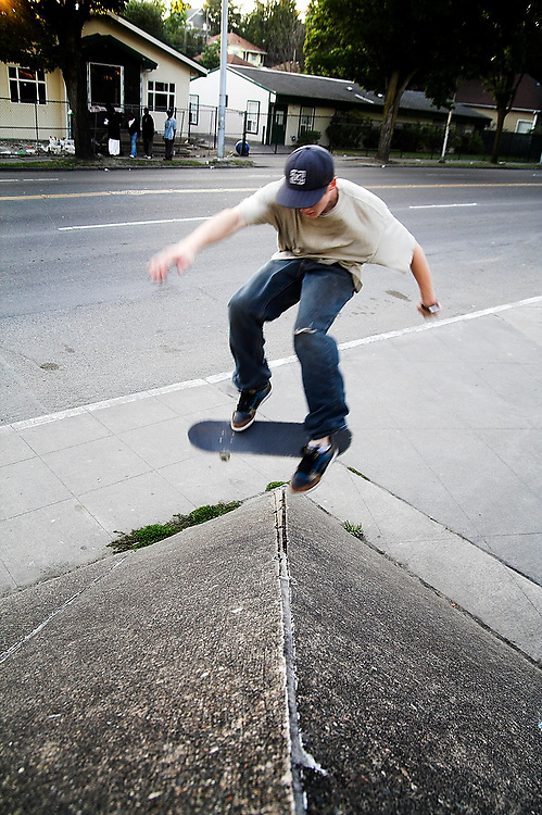 Trevor Fenner jumps over an angular concrete feature outside Medgar Evers Pool in Seattle, Washington. Houses and the city street are visible behind him. Fenner, who grew up in Seattle, now lives in Los Angeles and came back for the summer to look for work.