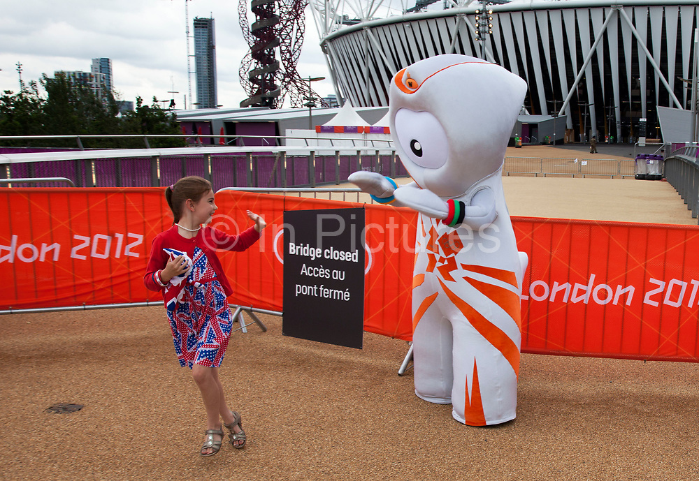 London 2012 Olympic Park in Stratford, East London. Happy and excited kids have their photo taken with Wenlock, one of the Olympic mascots. This little girl waves goodbye as she skips away.