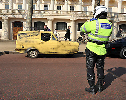 ©London News pictures. 08/03/11. The car from Only Fools and Horses is photographed by a police officer. Famous cars from TV and Film drive down the mall in London today (08/03/2011) as part of a publicity stunt for NetCars.com  Picture Credit should read Stephen Simpson/LNP