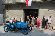 Locals wave goodbye as a visiting vintage car leaves a French village, during a three-day rally journey through the Corbieres wine region, on 26th May, 2017, in Lagrasse, Languedoc-Rousillon, south of France. Lagrasse is listed as one of Frances most beautiful villages and lies on the famous Route 20 wine route in the Basses-Corbieres region dating to the 13th century.