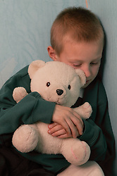 Young boy holding a teddy bear; looking alone and unhappy,