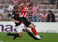 Photo: Pete Lorence.<br /> Lincoln City v Milton Keynes Dons. Coca Cola League 2. 16/09/2006.<br /> Paul Mitchell slides in against Scott Kerr of Lincoln City.
