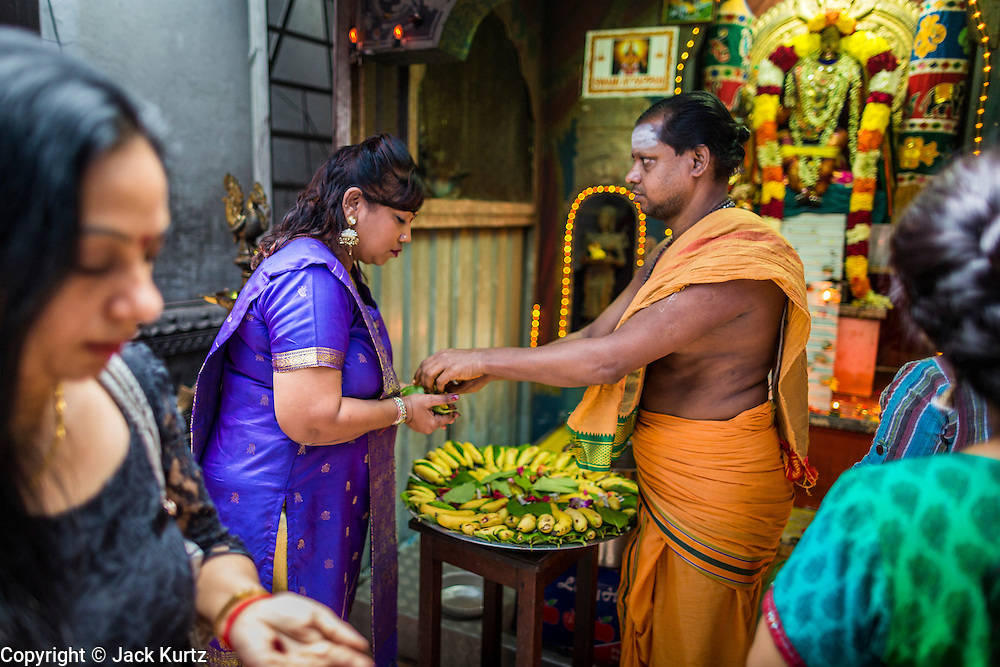 07 JANUARY 2014 - SINGAPORE:   A woman receives blessings from a Hindu priest during afternoon pooja at Sri Veeramakaliamman Temple, a Hindu temple located in Little India in the southern part of Singapore. The Sri Veeramakaliamman Temple is dedicated to the Hindu goddess Kali, fierce embodiment of Shakti and the god Shiva's wife, Parvati. Kali has always been popular in Bengal, the birthplace of the labourers who built this temple in 1881. Images of Kali within the temple show her wearing a garland of skulls and ripping out the insides of her victims, and Kali sharing more peaceful family moments with her sons Ganesha and Murugan. The building is constructed in the style of South Indian Tamil temples common in Tamil Nadu as opposed to the style of Northeastern Indian Kali temples in Bengal. PHOTO BY JACK KURTZ