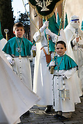 Young altar boys accompanying hooded penitents in a procession during Holy week in Salamanca, Spain. Street processions are organized in most Spanish towns each evening, from Palm Sunday to Easter Sunday. People carry statues of saints on floats or wooden platforms, and an atmosphere of mourning can seem quite oppressive to onlookers.