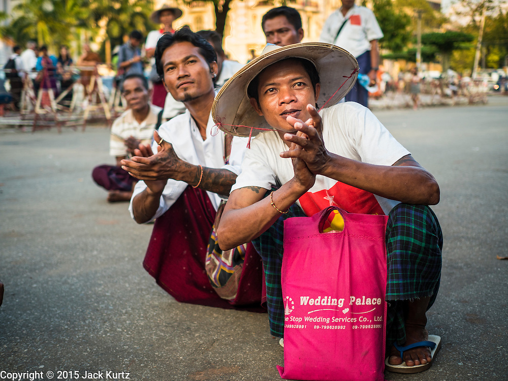 06 NOVEMBER 2015 - YANGON, MYANMAR: Men applaud the speakers at the final NDF election rally of the 2015 election. The rally was held in central Yangon, next to the historic Sule Pagoda and across the street from Yangon city hall. The National Democratic Force (NDF) was formed by former members of the National League for Democracy (NLD) who chose to contest the 2010 general election in Myanmar because the NLD boycotted that election. There have been mass defections from the NFD this year because many of the people who joined the NFD in 2010 have gone back to the NLD, which is contesting this year's election and widely expected to win it. Campaigning in the Myanmar election ended Friday. People go to the polls Sunday.     PHOTO BY JACK KURTZ