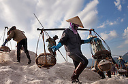 Under the blistering hot sun, women wearing heavy clothing mine salt from fields near Nha Trang on the Vietnam coast. The fields are flooded with ocean water and then the salt is mined when the water evaporates. Robert Dodge, a Washington DC photographer and writer, has been working on his Vietnam Unexpected project since 2005. The project has taken him throughout Vietnam, including Hanoi, Ho Chi Minh City (Saigon), Nha Trang, Mue Nie, Phan Thiet, the Mekong, Sapa, Ninh Binh and the Perfume Pagoda. His images capture scenes and people from women in conical hats planting rice along the Red River in the north to men and women working in the floating markets one the Mekong River and its tributaries. Robert's project also captures the traditions of ancient Asia in the rural markets, Buddhist Monasteries and the celebrations around Tet, the Lunar New Year. Also to be found are images of the emerging modern Vietnam, such as young people eating and drinking and embracing the fashions and music of the west. Robert Dodge, a Washington DC photographer and writer, has been working on his Vietnam Unexpected project since 2005. The project has taken him throughout Vietnam, including Hanoi, Ho Chi Minh City (Saigon), Nha Trang, Mue Nie, Phan Thiet, the Mekong, Sapa, Ninh Binh and the Perfume Pagoda. His images capture scenes and people from women in conical hats planting rice along the Red River in the north to men and women working in the floating markets one the Mekong River and its tributaries. Robert's project also captures the traditions of ancient Asia in the rural markets, Buddhist Monasteries and the celebrations around Tet, the Lunar New Year. Also to be found are images of the emerging modern Vietnam, such as young people eating and drinking and embracing the fashions and music of the West.