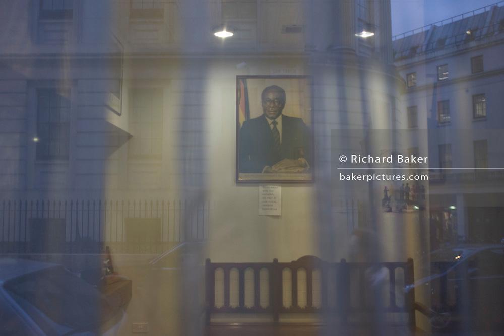 Framed portrait of Zimbabwe President Robert Mugabe through window of London embassy.