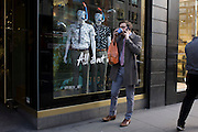 Man on smartphone and with coffee, is occupied by a display of eccentric mannequins in diving masks and snorkels, outside a central London branch of Ted Baker.