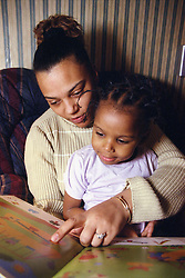Mother reading a book with young girl,