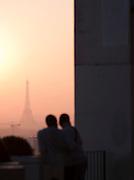 A couple watch sunset over the Eiffel Tower from Parc de Belleville, Paris, France