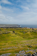 Tourists in the imposing Dun Aengus Stone Fort, Inishmore, the Aran Islands, off Ireland's west coast. The fort is preched on a windswept 100-metre high cliff above the Atlantic waves. Thought to date to the 2nd century BC,  it is surrounded by cheval de frise defences.