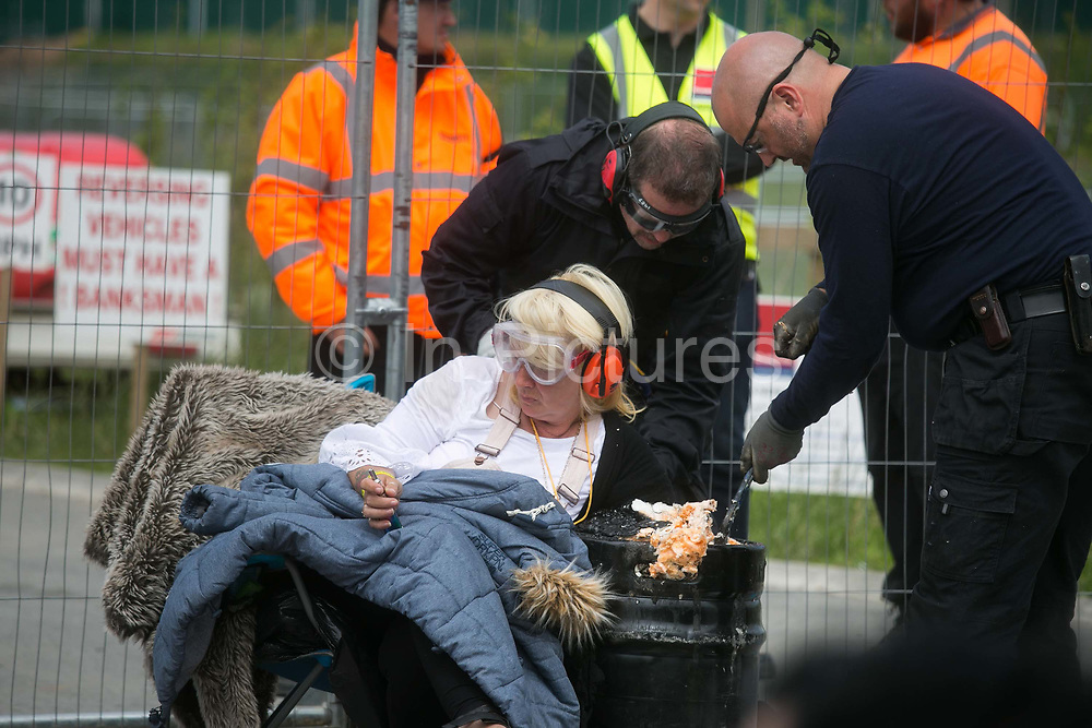 12 local activists locked themselves in specially made arm tubes to block the entrance to Quadrillas drill site in New Preston Road, July 03 2017, Lancashire, United Kingdom. Police specialist team cut Cath Robinson free after 12 hours.  The 13 activists included 3 councillors; Julie Brickles, Miranda Cox and Gina Dowding and Nick Danby, Martin Porter, Jeanette Porter,  Michelle Martin, Louise Robinson,<br /> Alana McCullough, Nick Sheldrick, Cath Robinson, Barbara Cookson, Dan Huxley-Blyth. The blockade is a repsonse to the emmidiate drilling for shale gas, fracking, by the fracking company Quadrilla. Lancashire voted against permitting fracking but was over ruled by the conservative central Government. All the activists have been active in the struggle against fracking for years but this is their first direct action of peacefull protesting. Fracking is a highly contested way of extracting gas, it is risky to extract and damaging to the environment and is banned in parts of Europe . Lancashire has in the past experienced earth quakes blamed on fracking.
