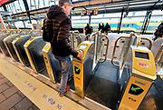 Nederland, Nijmegen, 1-2-2017Een treinreiziger houdt zijn ov-chipkaart tegen de kaartlezer. De poortjes op het station zijn gesloten zodat je niet zonder plaatsbewijs het perron op kan.Foto: Flip Franssen