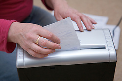 Woman shredding her receipts,