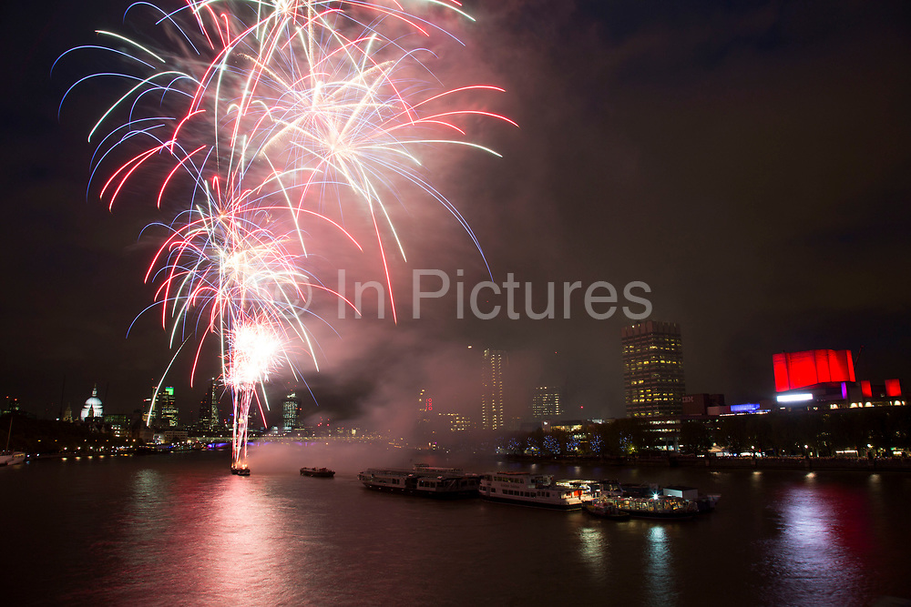 Skyline view of people gathered on the South Bank of the River Thames to watch the fireworks display for the Lord Mayor's Show in London, UK. The view provides an impressive lit up cityscape from St Paul's and the City of London, across to the National Theatre and the Southbank Centre.