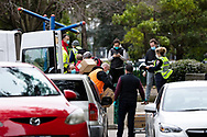 Government workers gather out side of  120 Racecourse Road as boxes of PPE are loaded on to a a trolley amid a full and total lockdown of 9 housing commission high rise towers in North Melbourne and Flemington during COVID-19 on 5 July, 2020 in Melbourne, Australia. After 108 new cases where uncovered overnight, the Premier Daniel Andrews announced on July 4 that effective at midnight last night, two more suburbs have been added to the suburb by suburb lockdown being Flemington and North Melbourne. Further to that, nine high rise public housing buildings in these suburbs have been placed under hard lockdown for a minimum of five days, effective immediately.  Residents in these towers will not be allowed to leave their units for any reason. Police will be stationed at every entry and exit point, every level, and they will also surround these locations preventing any movement in, or out. There is a total of 1354 units and over 3000 residents living in these buildings including the states most vulnerable people. These new restrictions will remain in place for fourteen days with fears of further lockdowns to come. The Government have stressed that if Victorians do not follow the basic COVIDSafe rules, the whole state will go back in to lockdown. (Image by Dave Hewison/ Speed Media)