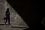 A woman walks into the shadows of London Fields arches while looking at her mobile phone on 27th May 2017 in London, United Kingdom. London Fields is a park and an area of historically common land adjoining the Hackney Central area of the London Borough of Hackney. From the series Our Small World, an observation of our mobile phone obsessions