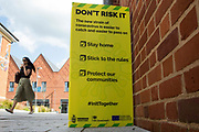 A woman passes a Covid-19 public information notice regarding the Delta variant on 14th July 2021 in Wokingham, United Kingdom. The leader of Wokingham Borough Council, John Halsall, has urged local residents to do all they can to avoid spreading the coronavirus as Covid-19 rates per 100,000 rise in the borough in advance of the planned lifting of national lockdown restrictions on 19th July.