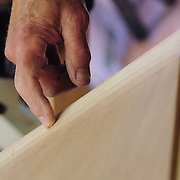 """Preparing the boat building kits  a few months before the event. Here a sloped """"scarf"""" is created to allow this 8' piece of plywood to be glued to a 4' scarfed piece to form one side of the 12' long hull shell."""