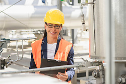 Portrait of a female engineer smiling with document at geothermal power station, Bavaria, Germany