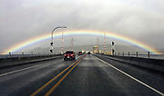 A perfectly symmetrical rainbow lines up with traffic on the Hood Canal Bridge on the edge of Jefferson County. This view looks northwest. (Ken Lambert/The Seattle Times)