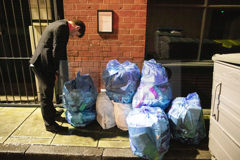 """© Licensed to London News Pictures . 22/12/2018 . Manchester , UK . A man urinates on to and then collapses over a pile of rubbish sacks on Jerusalem Place . Revellers out in Manchester City Centre overnight during """" Mad Friday """" , named for historically being one of the busiest nights of the year for the emergency services in the UK . Photo credit : Joel Goodman/LNP"""