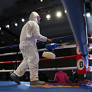 Cleaning crews disinfect the ring after each fight during a One For All Promotions boxing event at the Caribe Royale Orlando Events Center on Saturday, February 20, 2021 in Orlando, Florida. (Alex Menendez via AP)
