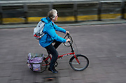 Een vrouw fietst op de vouwfiets in Amsterdam.<br /> <br /> A woman is cycling on her folding bike in Amsterdam.