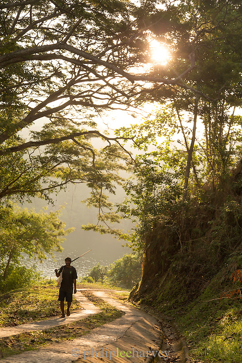 Man walking up hill at sunset, Tufi, Cape Nelson, Oro Province, Papua New Guinea
