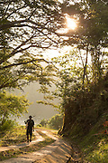 Man walking up hill at sunset, Tufi, Cape Nelson, Oro Province, Papua New Guinea
