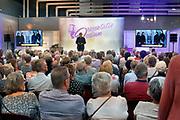 Nederland, Utrecht, 20-9-2018 Ouderen, senioren, bezoekers op de 50plus beurs. Charles Groenhuijsen houdt een voodracht. Hij wil dat we wat meer positief denken. Optimisme en geluk overkomen ons niet. Het is een keuze voor negatief of positief denken.Foto: Flip Franssen