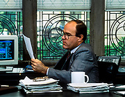 Executive reviews paperwork in his corporate office.
