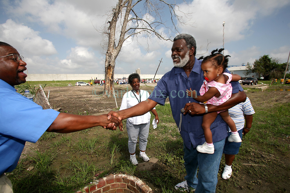 29 August 2006. New Orleans, Louisiana. Lower 9th ward. <br /> Returning home a year later and carrying his grand daughter Germain Saras (17mths), Charles Duplessis  meets old neighbours who gather at the site where their house used to stand close to the levee wall. Civilians gathered at the site of the breach of the industrial canal for the Great Flood commemoration and memorial ceremony to 'honor and remember our loved ones who have passed.' People came to mark the anniversary of devastating hurricane Katrina at the site where the now repaired and allegedly in theory stronger levee flood wall. The levee breached along the industrial canal at the point where people gathered, needlessly killing hundreds of innocent civilians in the worst engineering disaster in US history.<br /> Photo Credit©; Charlie Varley/varleypix.com