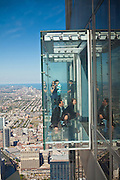 Tourists in the all glass balcony skydeck observation deck view the Chicago skyline103rd floor of the Willis Tower previously the Sears Tower.