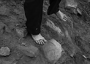 A barefoot pilgrim negotiates the rocks on Croagh Patrick mountain.