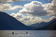 Kayakers paddle in the teal-blue waters of Lake Crescent, in Olympic National Park. (Bettina Hansen / The Seattle Times)