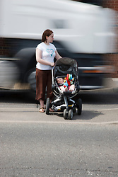 Mother trying to cross road with baby as traffic speeds by