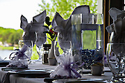 Table setting with purple accents overlooking trees and lake through window.