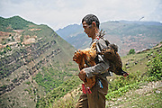LIANGSHAN, CHINA - MAY 14: (CHINA OUT) <br /> <br /> A man walks in Atuler village located at the 800-meter-high cliff on May 13, 2016 in Liangshan Yi Autonomous Prefecture, Sichuan Province of China. 72 families lived in Atuler village on the 800-meter cliff at Meigu River Canyon in Liangshan Yi Autonomous Prefecture. 15 pupils, aged 6 to 15, accompanied by 3 adults regularly spent 2 hours climbing 17 vines ladders hung on the 800-meter-high cliff to go between school and home twice a month. Villagers used the same ladders to go to the nearest market once a week to sell peppers and walnuts and buy necessities.<br /> ©Exclusivepix Media